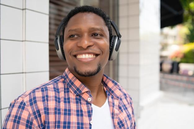 Homme afro-américain souriant et écoutant de la musique avec des écouteurs tout en se tenant à l'extérieur dans la rue.