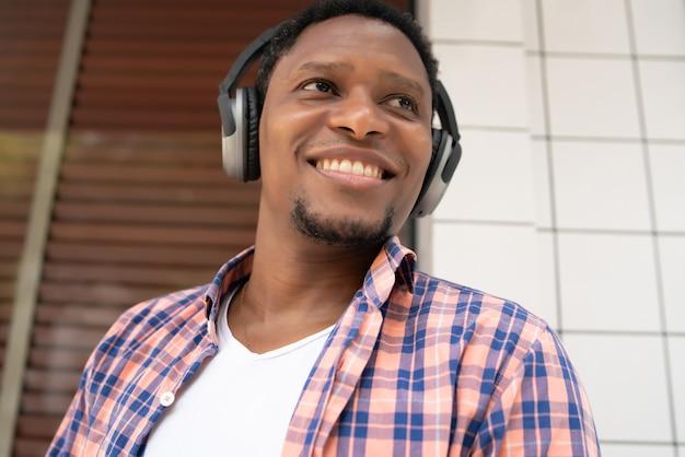 Homme afro-américain souriant et écoutant de la musique avec des écouteurs tout en se tenant à l'extérieur dans la rue