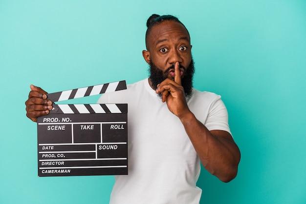 Homme afro-américain tenant un clap isolé sur fond bleu gardant un secret ou demandant le silence.