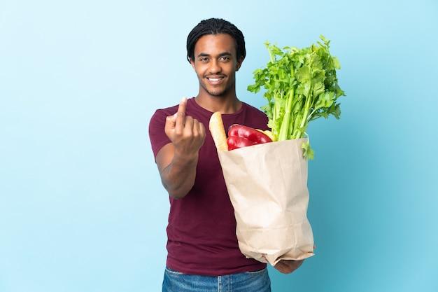 Homme afro-américain tenant un sac d'épicerie sur bleu faisant le geste à venir