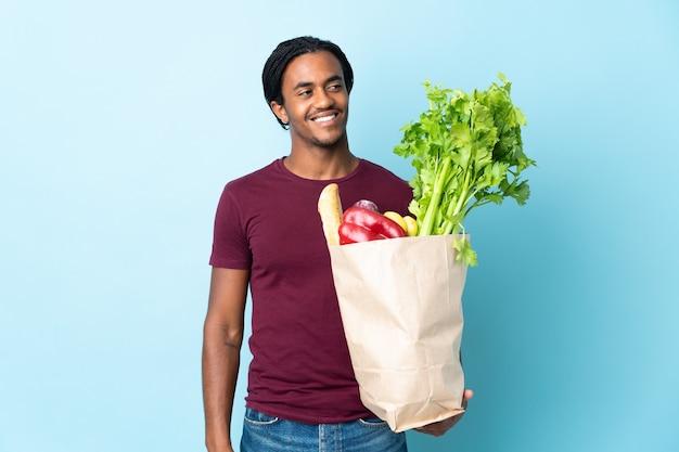 Homme afro-américain tenant un sac d'épicerie sur bleu pensant une idée tout en levant les yeux