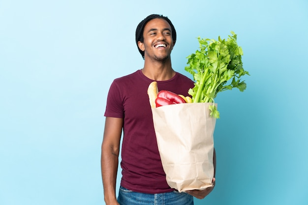 Homme afro-américain tenant un sac d'épicerie isolé sur fond bleu en riant