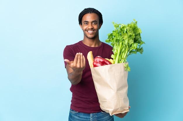 Homme afro-américain tenant un sac d'épicerie isolé sur un mur bleu invitant à venir avec la main.