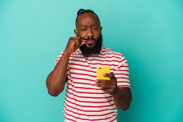 Homme afro-américain tenant un téléphone mobile isolé sur fond bleu