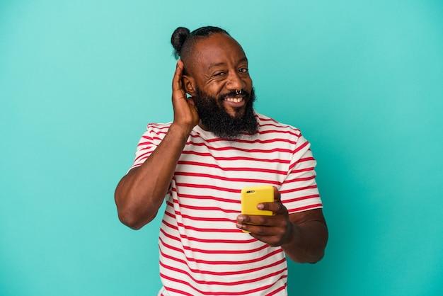 Homme afro-américain tenant un téléphone portable isolé sur fond bleu essayant d'écouter un potin.