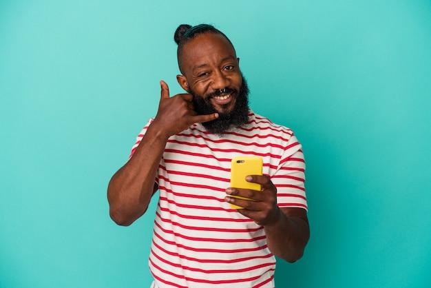 Homme afro-américain tenant un téléphone portable isolé sur fond bleu montrant un geste d'appel de téléphone portable avec les doigts.