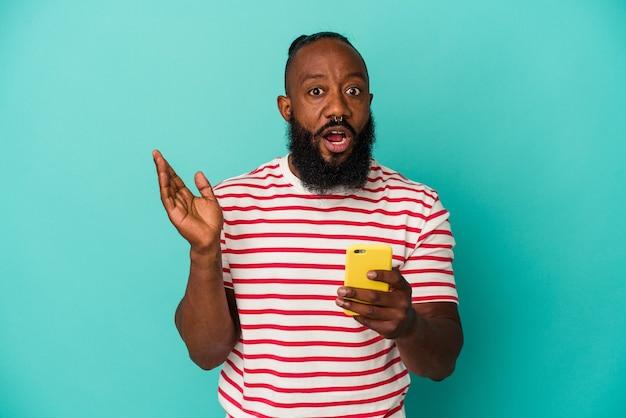Homme afro-américain tenant un téléphone portable isolé sur fond bleu surpris et choqué