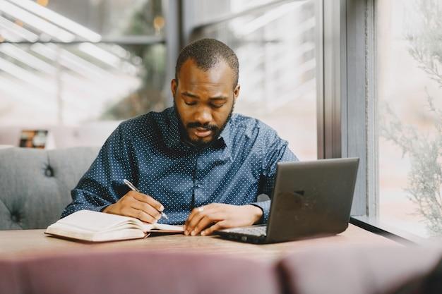 Homme afro-américain travaillant derrière un ordinateur portable et écrivant dans un cahier. homme à la barbe assis dans un café.
