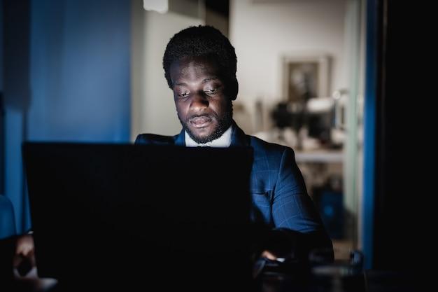 Homme afro-américain travaillant la nuit à l'intérieur d'un bureau moderne - focus on face