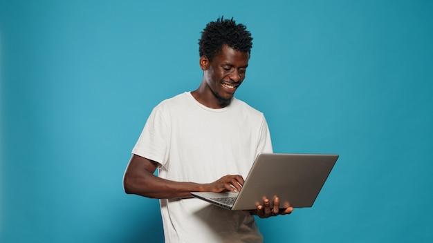 Homme afro-américain utilisant un ordinateur portable pour se divertir