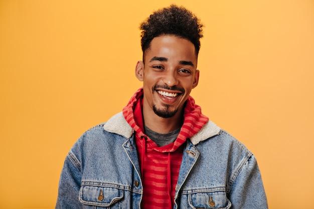 Homme afro-américain en veste en jean souriant sur un mur orange