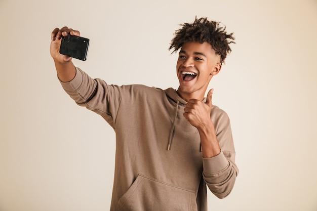 Homme afro-américain vêtu d'un sweat à capuche prenant un selfie isolé tout en montrant le geste du pouce vers le haut.