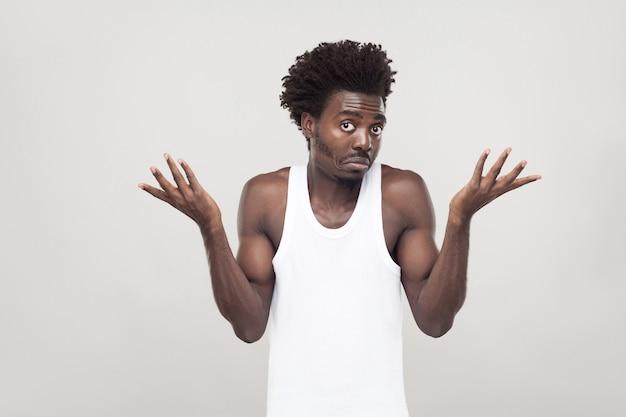 L'homme afro émotionnel a un regard confus. prise de vue en studio. fond gris