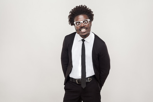 Homme afro idiot à lunettes blanches grimaçant à la caméra. prise de vue en studio, fond gris