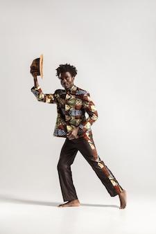 Homme afro séduisant tenant un chapeau et regardant la caméra. intérieur, isolé sur fond gris