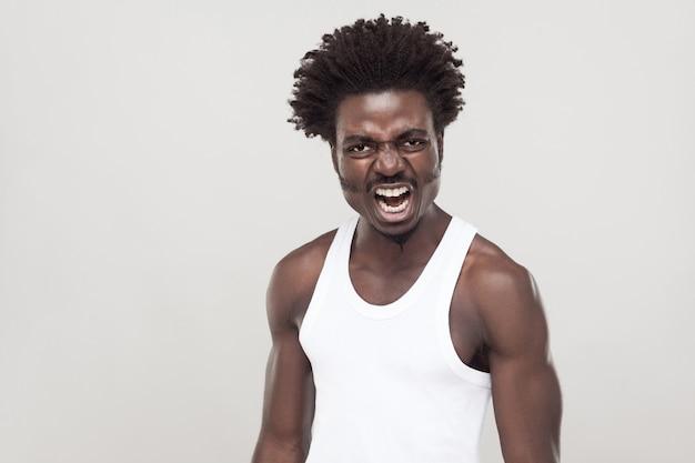 Homme afro en t-shirt blanc criant à la caméra. prise de vue en studio. fond gris