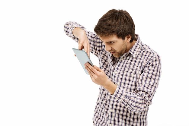 Homme agacé appuyez sur une tablette numérique