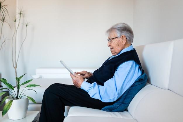 Homme âgé à l'aide d'une tablette numérique
