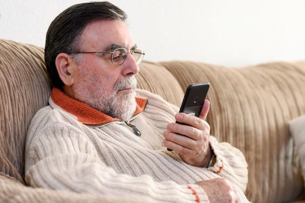 Un homme âgé à l'aide de téléphone portable assis sur un canapé à la maison, pendant la quarantaine du coronavirus.