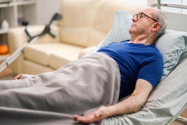 Homme âgé allongé dans une maison de soins infirmiers avec une canule sur son bras.