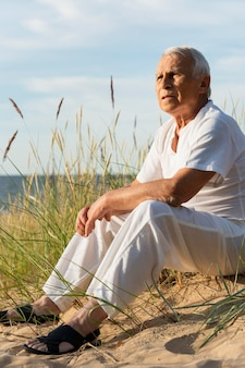 Homme âgé appréciant la vue sur la plage