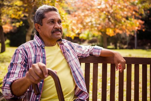 Un homme âgé assis sur le banc avec sa canne