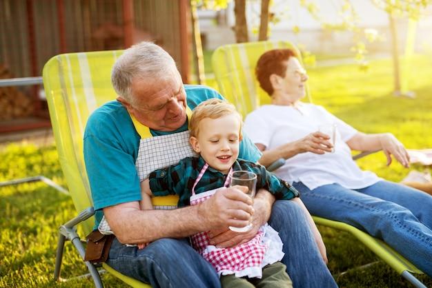 Un homme âgé assis sur une chaise dans le jardin tenant son petit-fils souriant et lui offrant de l'eau.