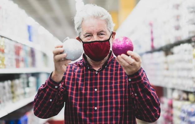 Un homme âgé aux cheveux blancs tenant deux boules de noël scintillantes, argentées et violettes, portant un masque médical en raison d'une infection à coronavirus