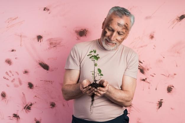 Un homme âgé aux cheveux gris avec une barbe tient une plante dans ses mains, il l'examine attentivement