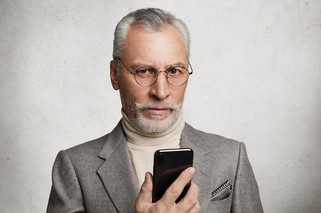Homme âgé aux cheveux gris barbu habillé en costume formel