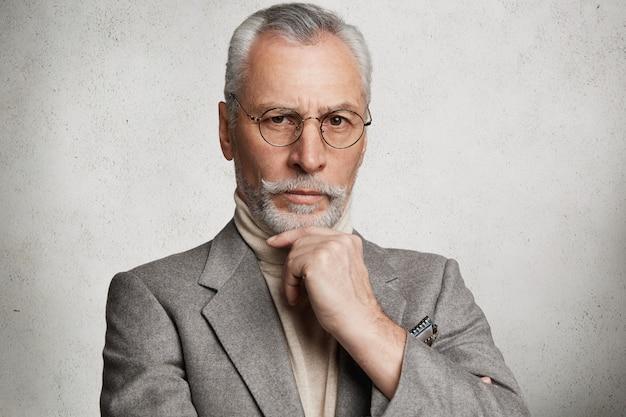Homme âgé aux cheveux gris barbu portant un costume formel