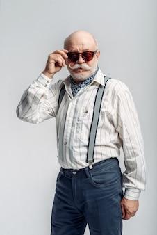 Homme âgé barbu avec moustache pose dans des lunettes de soleil. senior mature