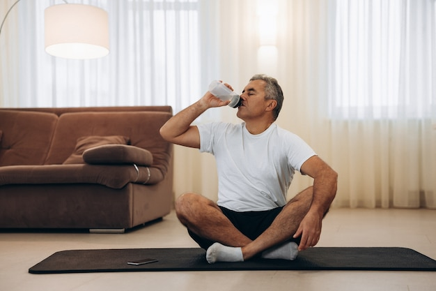Un homme âgé boit de l'eau après le yoga et s'assoit avec les jambes croisées