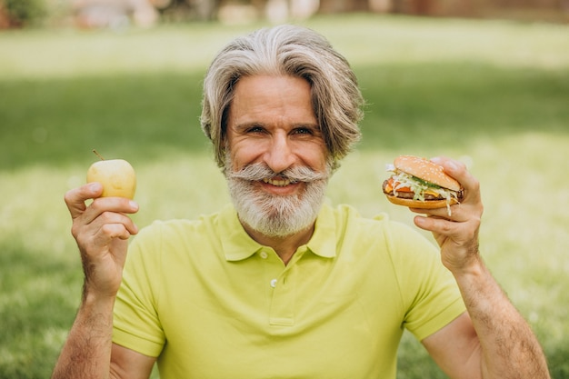 Homme âgé de choisir entre hamburger et pomme