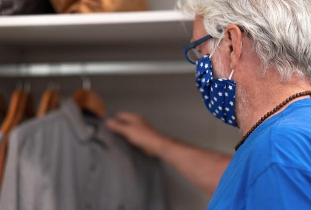 Un homme âgé choisit une chemise dans sa garde-robe portant un masque de protection à cause du coronavirus