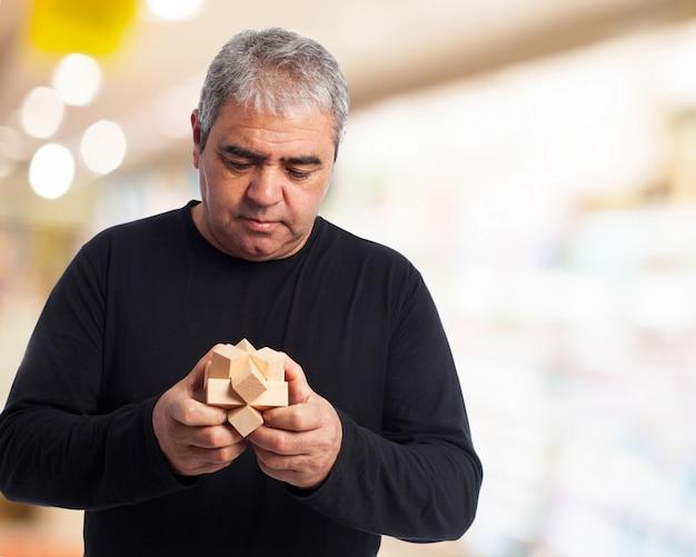 Un homme âgé de concentration avec un jouet en bois