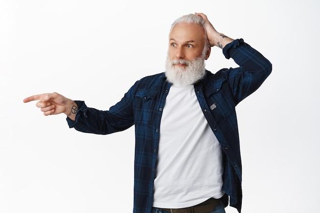 Un homme âgé confus pointe le doigt vers quelque chose de surprenant, se gratte la tête et regarde avec admiration, regarde quelque chose de cool, regarde là un geste, debout sur un mur blanc
