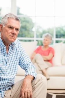 Homme âgé contrarié après s'être disputé avec sa femme dans le salon
