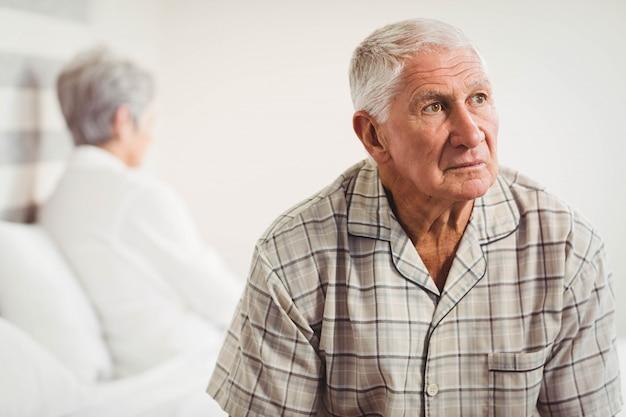 Homme âgé contrarié assis aux extrémités opposées du lit après une bagarre