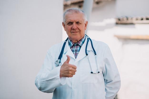 Un homme âgé dans une blouse blanche et un masque médical sur son visage montre un stéthoscope pour examiner le travail des poumons et du cœur des patients