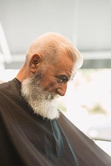Homme âgé dans un salon de coiffure