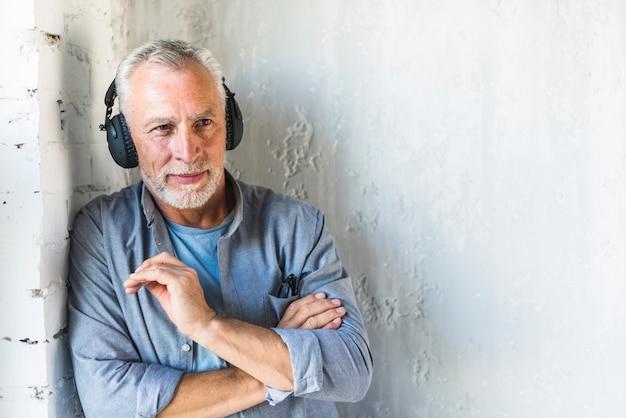 Homme âgé, debout, contre, mur, écoute, musique, sur, écouteur