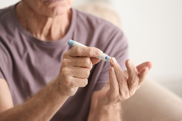 Un homme âgé avec diabète mesurant le niveau de sucre dans le sang à la maison, gros plan