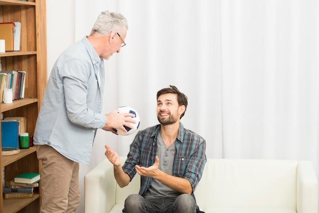 Homme âgé donnant sa balle à un jeune homme sur un canapé