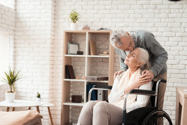 Un homme âgé embrasse une femme d'âge mûr au front en fauteuil roulant.