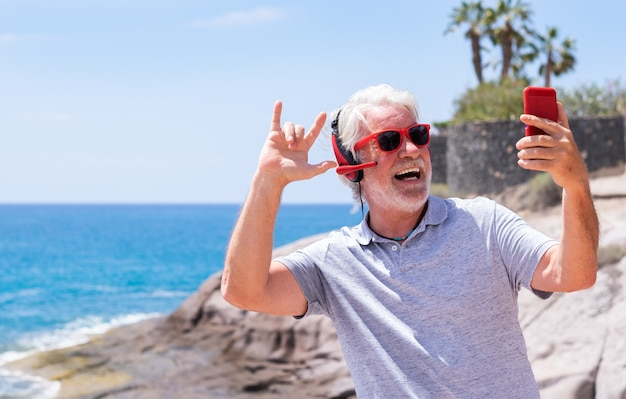 Un homme âgé enjoué exprime le bonheur et la joie tout en se tenant au bord de la mer lors d'un appel vidéo avec un téléphone portable