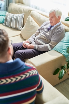 Un homme âgé expliquant ses sentiments à un psychiatre