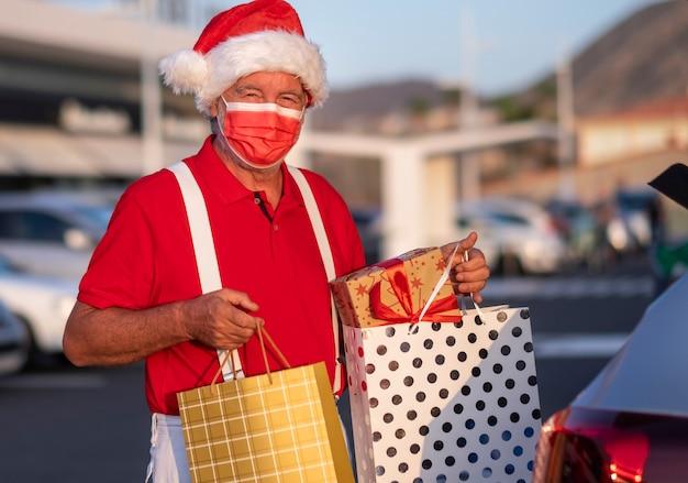 Un homme âgé faisant du shopping pour noël dans un bonnet de noel et des bretelles met des sacs avec des cadeaux dans la voiture