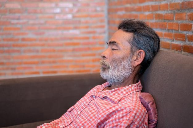 Un homme âgé faisant une sieste dans un canapé à la maison.