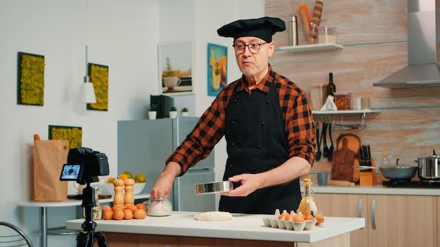 Un homme âgé gai enregistrant la recette étape par étape dans la cuisine de la houe. chef influenceur blogueur à la retraite utilisant la technologie internet pour communiquer, bloguer sur les réseaux sociaux avec un équipement numérique